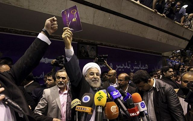 Iranian presidential candidate Hasan Rowhani, center, holds up a leaflet showing a key, the symbol of his campaign, during a rally in Tehran, Iran, Saturday, June 8 (photo credit: AP/Ebrahim Noroozi)