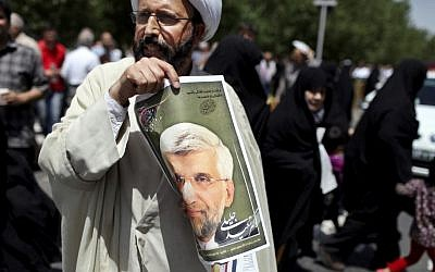 An Iranian cleric holds up a poster of presidential candidate Saeed Jalili, Iran's top nuclear negotiator, after the Friday prayer in Tehran, Friday, May 31, 2013. Iranians have seen it before: A youngish presidential candidate firing up crowds with fist-waving rants against the West, then displaying his Islamist bona fides with courtesy calls to hard-line clerics. (AP Photo/Ebrahim Noroozi)