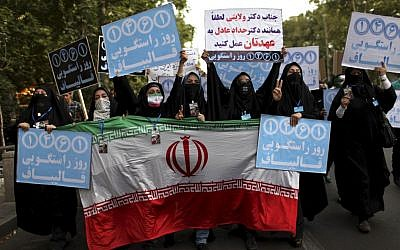 Female supporters of the Iranian presidential candidate Mohammad Bagher Qalibaf, who is also Tehran's mayor, hold placards in Tehran, Iran, on Tuesday, June 11, 2013. (photo credit: AP/Ebrahim Noroozi)