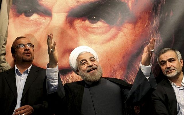 Hasan Rouhani, center, poses before a large portrait of the late Iranian revolutionary founder Ayatollah Khomeini, the day after being elected to Iran's presidency, on June 15, 2013 (Photo credit: AP/Ebrahim Noroozi)