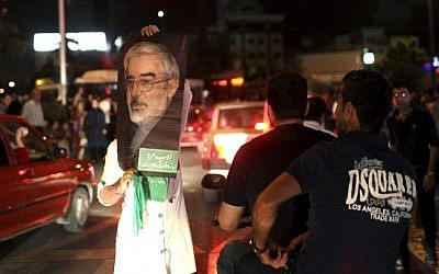 A supporter of Iranian presidential candidate Hasan Rowhani holds up a poster of Green Movement leader Mir Hossein Mousavi, who was a candidate in 2009 and is currently under house arrest, while celebrating Rowhani's victory, in Tehran, Saturday, June 15, 2013.  (photo credit: AP Photo/Ebrahim Noroozi)