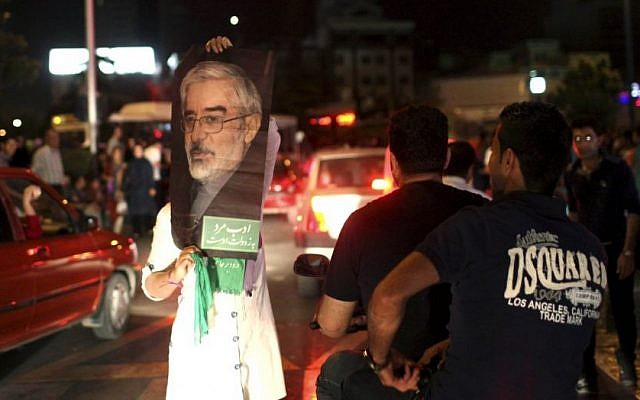 A supporter of Iranian presidential candidate Hasan Rouhani holds up a poster of Green Movement leader Mir Hossein Mousavi, while celebrating Rouhani's victory, in Tehran, Saturday, June 15, 2013.  (AP/Ebrahim Noroozi)