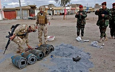 In this file photo taken on Jan. 16, 2012, Iraqi security forces inspect bombs at the scene of a car bomb attack outside the northern city of Mosul, 225 miles (360 kilometers) northwest of Baghdad, Iraq. (photo credit: AP, file)