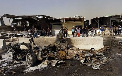 Illustrative photo of Iraqis inspecting the scene of a car bomb attack in the Ameen neighborhood of eastern Baghdad, Iraq (photo credit: AP/ Khalid Mohammed)