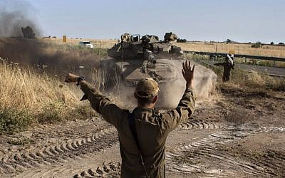 An Israeli soldier directs a tank near the Quneitra crossing with Syria on Thursday.(photo credit: AP/Sebastian Scheiner)
