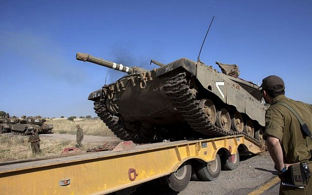An Israeli tank is loaded onto a truck near the Quneitra crossing with Syria, on Thursday, June 6, 2013. (photo credit: AP/Sebastian Scheiner)