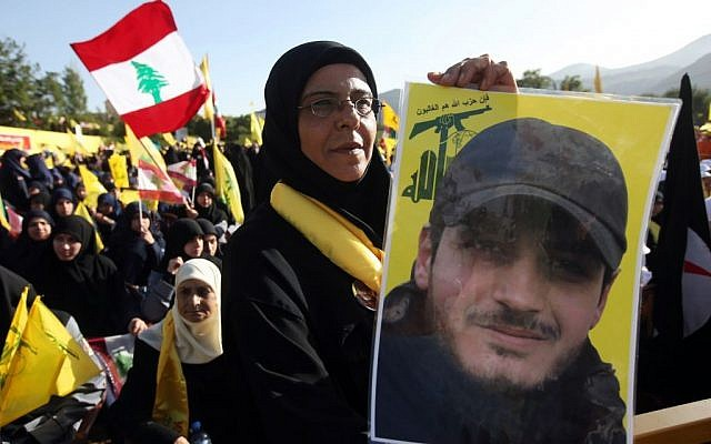 In this picture taken on Saturday May 25, 2013, a Hezbollah supporter holds a portrait of her son, Ibrahim Kanso, 24, who was killed 40 days before, at Sayida Zeinab shrine during a battle in Syria against the Syrian rebels (photo credit:AP/Hussein Mella)