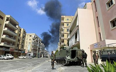 Lebanese army soldiers stand while black smoke rises from a burning house that was attacked during clashes that erupted between followers of a radical Sunni cleric Sheik Ahmad al-Assir and Shiite gunmen in Sidon, Lebanon, Monday, June 24, 2013 (photo credit: AP/Bilal Hussein)