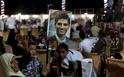 A Palestinian woman waves a picture of Palestinian singer Mohammed Assaf while watching the contestant perform in a regional TV singing contest, in Gaza City on Saturday, June 22, 2013. (photo credit: AP Photo/Hatem Moussa)