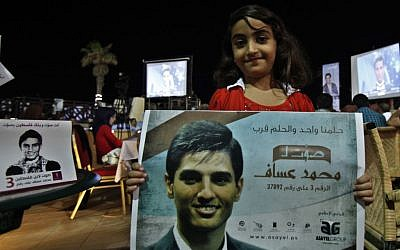 A Palestinian girl carries a poster of singer Mohammed Assaf, 23, while watching the televised performance of the Palestinian finalist on the Arab Idol talent show, in Gaza City, Friday, June 21 (photo credit: AP/Adel Hana)
