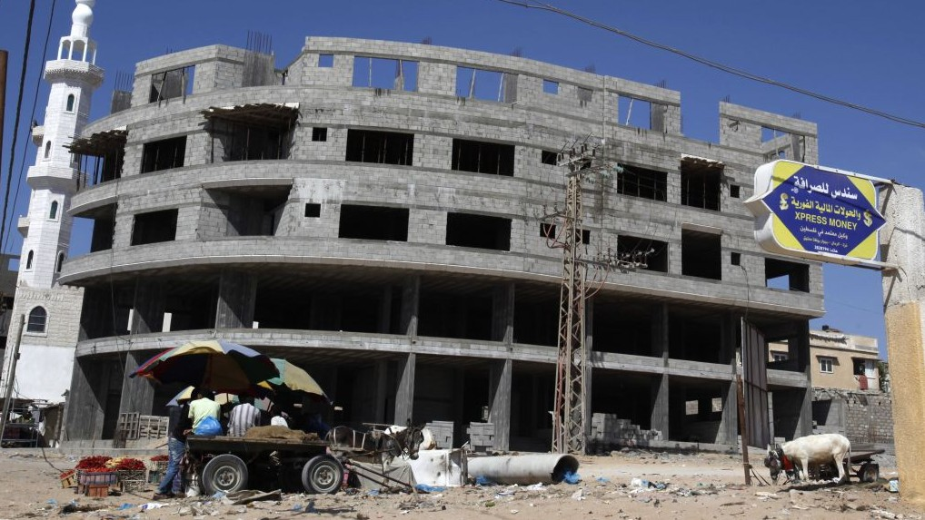 Palestinian vendors sit in front of a building under construction at the main road in Gaza City, Thursday, June 27, 2013 (photo credit: AP/Adel Hana)