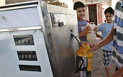 A Palestinian employee fills a container with Israeli diesel at gas station in Gaza City, Thursday, June 27, 2013 (photo credit: AP/Adel Hana)