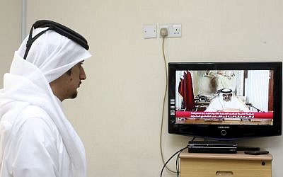 A man watches a televised address by Qatar's Emir Sheik Hamad bin Khalifa Al Thani, in Doha, Qatar,Tuesday, June 25, 2013 (photo credit: AP/Osama Faisal)