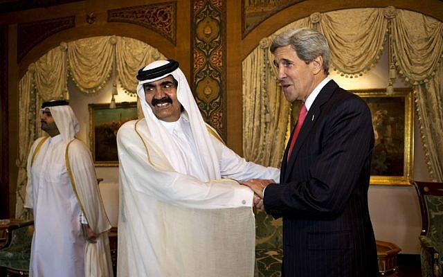 U.S. Secretary of State John Kerry, right, is greeted by Qatari Emir Hamad bin Khalifa Al Thani at Wajbah Palace in Doha, Qatar, on Sunday, June 23, 2013 (photo credit: AP/Jacquelyn Martin)