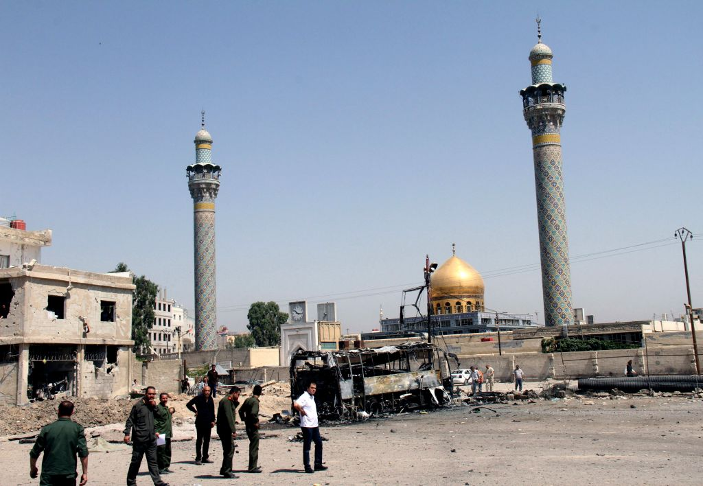 Syrian security forces at the site where a car bomb exploded near the Shi'ite shrine of Sayyida Zeinab, visible in the background, near Damascus, Syria in June 2012. (photo credit: /Bassem Tellawi, AP File)