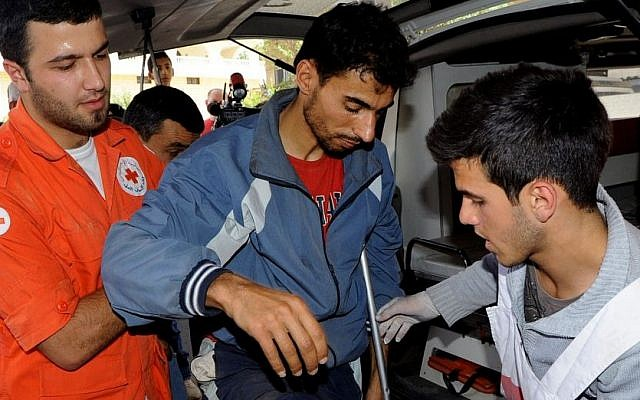 Members of the Lebanese Red Cross help a Syrian man who was wounded in Qusair, Syria, during battles between the rebels and the Syrian government forces, at a hospital in the Bekaa Valley, east of Beirut, Lebanon, on Saturday, June 8, 2013. (photo credit: AP/file photo)