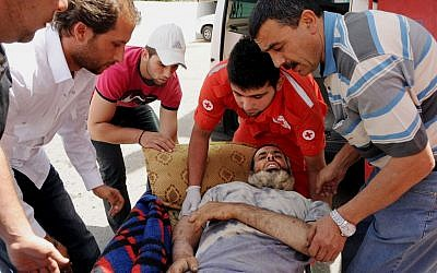 Members of the Lebanese Red Cross carry a Syrian man who was wounded in Qusair during battles between the rebels and Syrian government forces, Saturday, June 8, 2013 (photo credit: AP)