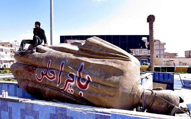 """This Tuesday, March 5, 2013 file photo shows a Syrian man sitting on a fallen statue of former Syrian president Hafez Assad in a central square in Raqqa, Syria. The Arabic words on the fallen statue read: """"tomorrow will be better."""" (Photo credit: AP/Aleppo Media Center AMC)"""