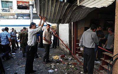 In this photo released by the Syrian official news agency SANA, Syrians inspect a damaged shop at a scene of two explosions in the central district of Marjeh, Damascus, Syria, Tuesday, June 11, 2013 (photo credit: AP/SANA)