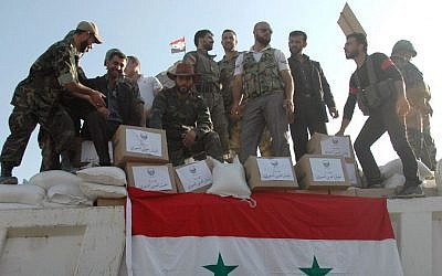 Syrian soldiers loyal to President Bashar Assad stand on a truck full of aid supplies, in Qusair, Syria, June 5, 2013. (photo credit: AP/SANA/File)