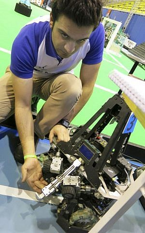 Mostafa Mahmoodi, in charge of mechanical systems for the robotics team from Iran's Qazvid Islamic Open University, shows off the kicking and passing device used by his mid-sized robots at the RoboCup in Eindhoven, Netherlands, on Thursday, June 27, 2013. (photo credit: AP Photo/Toby Sterling)
