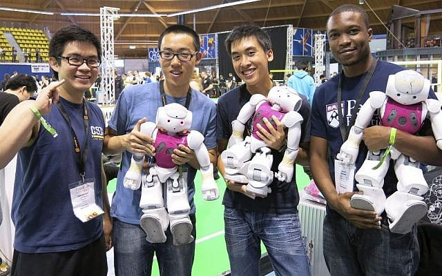 "Chris Akatsuka, Dickens He, Alan Aquino and Tatenda Mushonga from the University of Pennsylvania's ""UPennalizer"" team show off their robots at the RoboCup championships in Eindhoven, Netherlands, on June 27, 2013. (photo credit: AP Photo/Toby Sterling)"