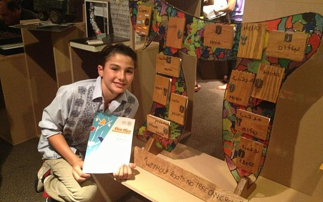 Gianni Mizrahi, 11, from San Diego, CA, poses with his first-place winning display for 'My Family Story,' a competition held by the Beit Hatfutsot, the Museum of the Jewish People, in Tel Aviv (photo credit: Leeor Bronis/Times of Israel)