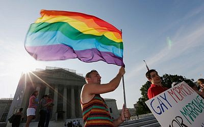 Illustrative photo. Gay rights supporter waving a rainbow flag outside the US Supreme Court building in Washington following its ruling expanding gay rights, June 26, 2013. (Win McNamee/Getty Images via JTA)