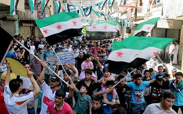 Anti-Syrian regime protesters holding Syrian revolution flags, during a demonstration in the neighborhood of Bustan Al-Qasr in Aleppo, Syria, Friday, June 28, 2013 (photo credit: AP Photo/Aleppo Media Center AMC)