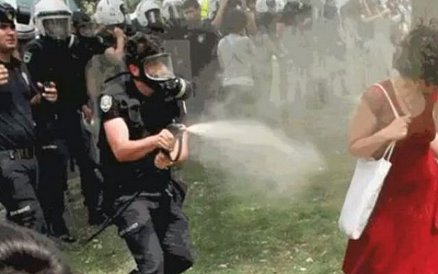 The woman attempts to escape the tear-gas cloud (photo credit: Youtube screenshot)