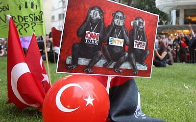 In this Sunday, June 2, 2013 photo protesters display a banner depicting Turkish media as the three wise monkeys who see no evil, speak no evil and hear no evil, outside Haber Turk television channel in Istanbul.(photo credit: AP/Thanassis Stavrakis)