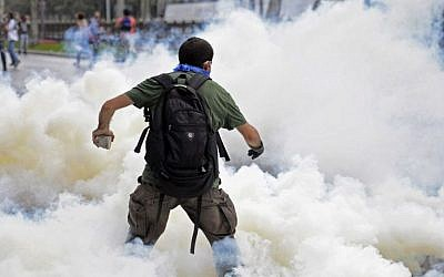 A man runs as riot police use tear gas and pressurized water to quash a sit-in protest to try and prevent the demolition of trees at an Istanbul park, Turkey, Friday, May 31, 2013. Police moved in at dawn Friday to disperse the crowd on the fourth day of the protest against a contentious government plan to revamp Istanbul's main square, Taksim. (AP Photo)