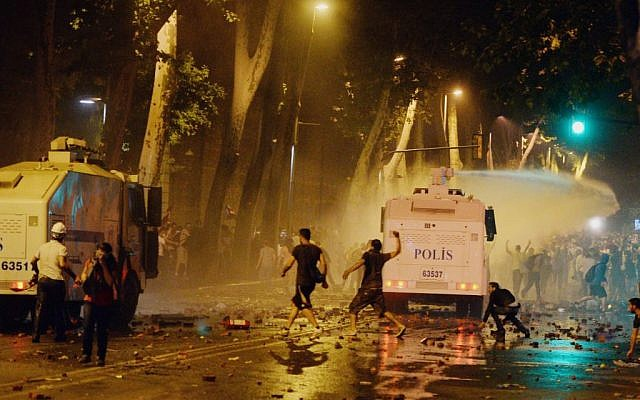 In this photo taken late Saturday, June 1, 2013, Turkish protesters clash with riot police near the former Ottoman palace, Dolmabahce, where Turkey's Prime Minister Recep Tayyip Erdogan maintains an office in Istanbul, Turkey. (photo credit: AP)