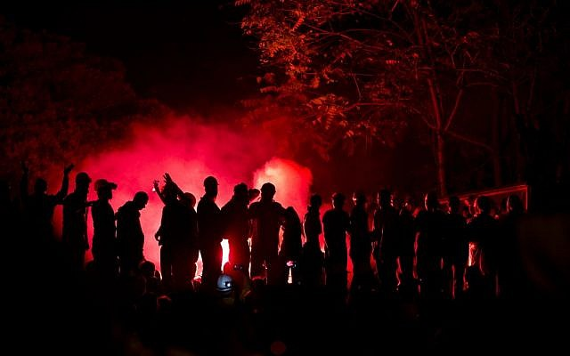 Protesters chant anti-government slogans, silhouetted by the light of flares in Taksim square, in Istanbul, Turkey, late Wednesday, June 12 (photo credit: AP/Vadim Ghirda)