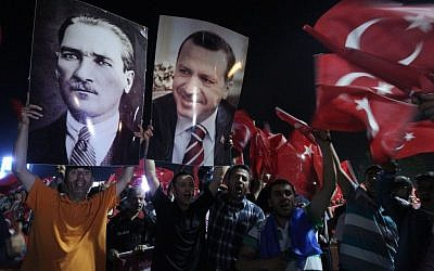 Supporters of the AKP, Justice and Development party hold the portraits of Mustafa Kemal Ataturk, founder of Turkey and Turkish Prime Minister Recep Tayyip Erdogan at the Ataturk Airport of Istanbul early Friday, June 7, 2013. (AP Photo/Thanassis Stavrakis)