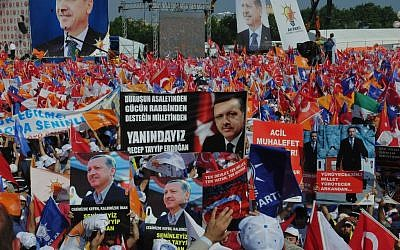 Supporters of Turkish Prime Minister Recep Tayyip Erdogan wave his posters before he arrives to address a party rally in Istanbul on Sunday, June 16, 2013. The banner at the center reads: 'We are with you.' (photo credit: Burhan Ozbilici/AP)