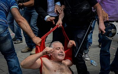 Turkish police detain a demonstrator who remained defiant after authorities evicted activists from Istanbul's Taksim Park on Sunday, June 16, 2013.(photo credit: Burhan Ozbilici/AP)