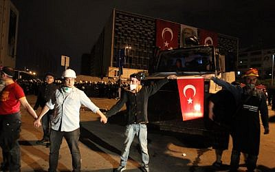 Protesters form a human chain in front of police forces at Taksim Square in Istanbul late Wednesday, June 12, 2013. (Photo credit: AP/Thanassis Stavrakis)