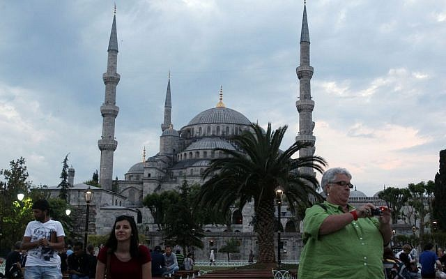 Illustrative: Tourists take photographs in front of the Blue Mosque in Sultanahmet tourist area of Istanbul, late Tuesday, on June 4, 2013. (AP Photo/Thanassis Stavrakis)