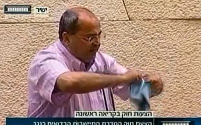Ahmad Tibi, in the Knesset plenum in June, tears a bill regulating the Bedouin settlements in the Negev. (photo credit: screen capture/Knesset Channel)