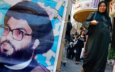 A Palestinian woman walks past a poster of Hezbollah chief Sayyed Hassan Nasrallah in the West Bank town of Ramallah on 09 August 2006 (photo credit: Olivier Fitoussi/Flash90)