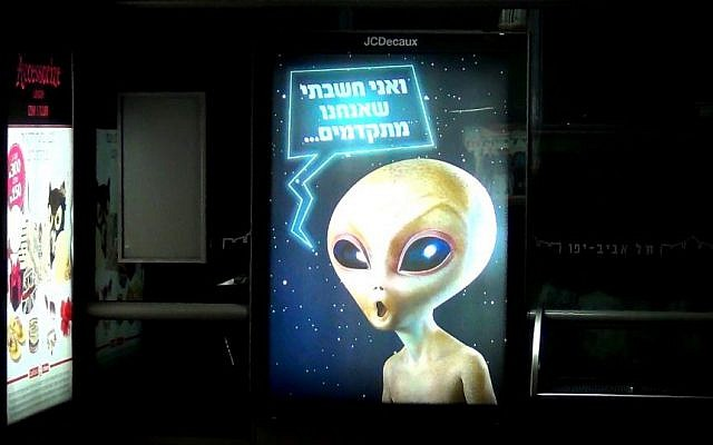 "An advertisement campaign for Kiddum featuring an image of an alien,  Rothschild Blvd, Tel Aviv. The ad copy reads: ""And I thought that we were advanced..."" (photo credit: Ricky Ben-David/Times of Israel)"