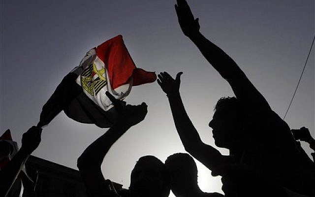 Egyptian protesters shout anti-Muslim brotherhood slogans and wave a national flag during a protest against the new judiciary law at the high court in Cairo, Egypt, Monday, June 3, 2013.(photo credit: AP Photo/Amr Nabil)