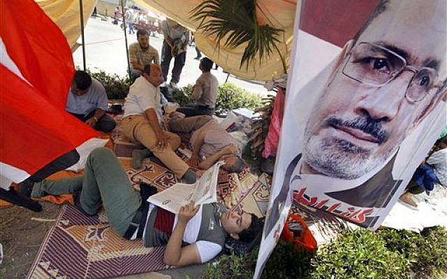 Supporters of Egypt's Islamist President Mohammed Morsi rest at their tent with a poster of the president at a public square outside the Rabia el-Adawiya mosque near the presidential palace in Cairo, Saturday, June 29, 2013 (photo credit: AP Photo/Amr Nabil)