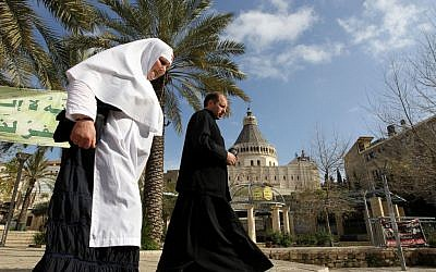 A nun and a priest pass by the Basilica of the Annunciation in  Nazareth (photo credit: Nati Shohat/Flash 90)