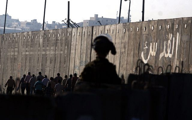 An IDF soldier watches as Palestinians cross into Jerusalem from the Qalandiya checkpoint near the West Bank city of Ramallah. (Issam Rimawi/Flash90)