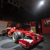 A Ferrari technical crew member stands next to a Ferrari Formula One racing car, on display during a racing car and motorcycle exhibition held at the Old Jerusalem Train Station, on June 9, 2013 (photo credit: Flash90)