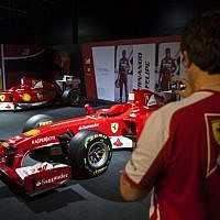 A Ferrari technical crew member takes a photograph of Ferrari Formula One racing cars, on display during a racing car and motorcycle exhibition held at the Old Jerusalem Train Station, on June 9, 2013 (photo credit: Flash90)