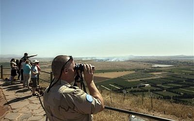 A UN soldier looks through binoculars towards Syria from an observation point on Mt. Bental in the Golan Heights as smoke rises from nearby fighting in Syria, Friday, June 7, 2013 (photo credit: AP Photo/Sebastian Scheiner)