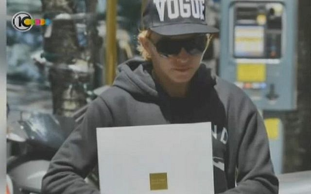Madonna with a brochure for a Tev Aviv apartment tower. CLICK HERE TO ENLARGE (photo credit: Channel 10 screen capture)